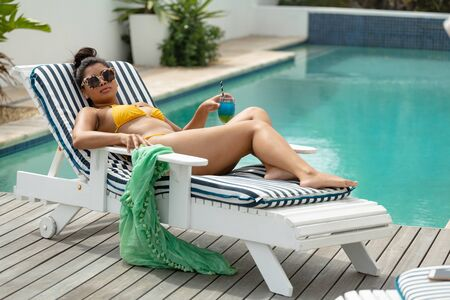 Side view of beautiful mixed-race woman in bikini relaxing on a sun lounger near swimming pool at the backyard of home. Summer fun at home by the swimming pool