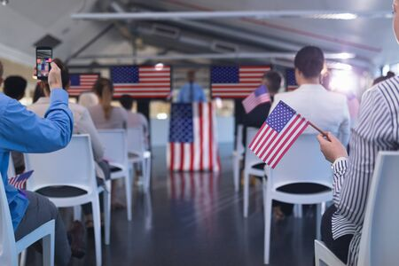 Widok z przodu różnych ludzi biznesu wymachując amerykańską flagą w seminarium biznesowym. Koncepcja międzynarodowego zróżnicowanego partnerstwa biznesowego korporacyjnego