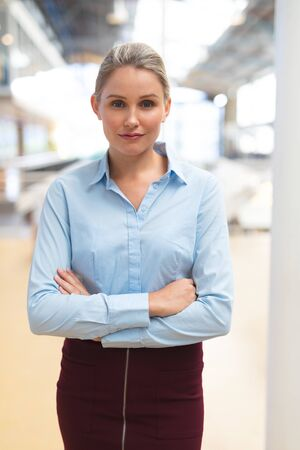Portrait of Caucasian businesswoman standing with arms crossed in the corridor at office. International diverse corporate business partnership concept Stock Photo