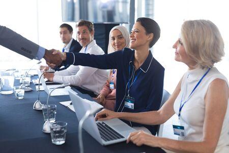 Seitenansicht verschiedener Geschäftsleute, die sich beim Einchecken des Geschäftsseminars beim Konferenztreffen die Hände schütteln. Internationales vielfältiges Corporate Business Partnership-Konzept