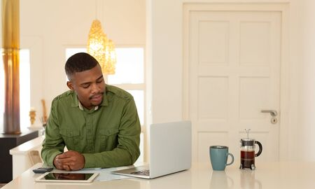 Front view of African-american man working on laptop at dining table in kitchen at comfortable home. Authentic home lifestyle setting with young African American male