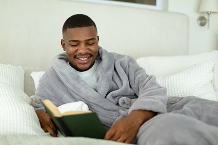 Side view of happy African-american man reading a book while lying on bed in bedroom at comfortable home. Authentic home lifestyle setting with young African American male
