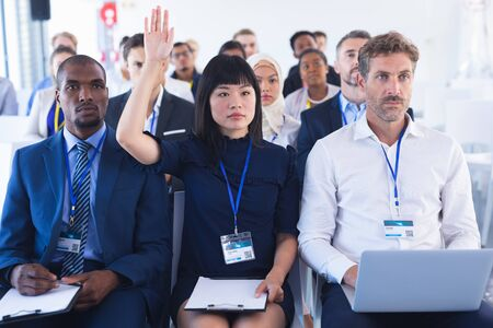Front view of diverse Businesswoman raising her hand while attending business seminar in conference meeting. International diverse corporate business partnership concept Imagens