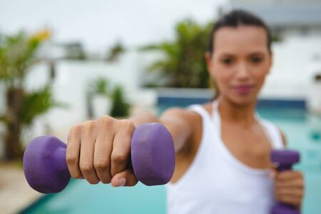 Close-up of mixed-race woman exercising with dumbbells near swimming pool in the backyard. Summer fun at home by the swimming pool