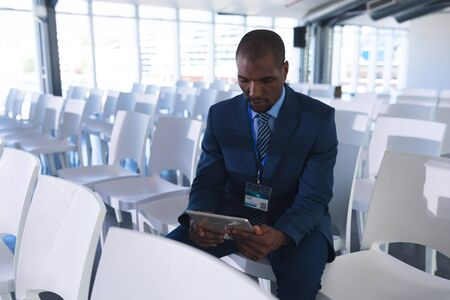 Front view of African-american Male speaker practicing his speech on digital tablet in business seminar at conference room. International diverse corporate business partnership concept