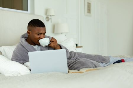Side view of African-american man drinking coffee while using laptop on bed in bedroom at comfortable home. Authentic home lifestyle setting with young African American male Reklamní fotografie
