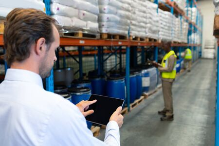 Rear view of mature Caucasian male supervisor working on digital tablet in warehouse. African-american colleagues working in front of him. This is a freight transportation and distribution warehouse. Industrial and industrial workers concept
