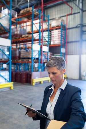 Close-up of beautiful mature Caucasian female manager checking stocks on clipboard in warehouse. This is a freight transportation and distribution warehouse. Industrial and industrial workers concept