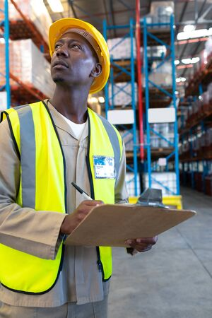 Close-up of concentrated African-american male worker looking away while writing on clipboard in warehouse. This is a freight transportation and distribution warehouse. Industrial and industrial workers concept