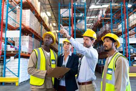 Front view of Caucasian male supervisor standing with diverse coworkers and pointing at distance in warehouse. This is a freight transportation and distribution warehouse. Industrial and industrial workers concept
