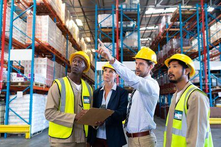 Vista frontal del supervisor masculino caucásico de pie con diversos compañeros de trabajo y apuntando a la distancia en el almacén. Se trata de un almacén de transporte y distribución de mercancías. Concepto de trabajadores industriales e industriales