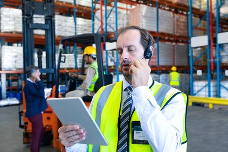 Close-up of handsome Caucasian male supervisor using digital tablet while talking on headset in warehouse. Diverse colleagues communicating in the background. This is a freight transportation and distribution warehouse. Industrial and industrial workers concept