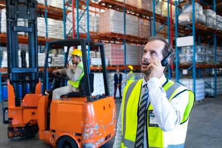Front view of handsome Caucasian male supervisor talking on headset in warehouse. Diverse colleagues working in the background. This is a freight transportation and distribution warehouse. Industrial and industrial workers concept Stock fotó