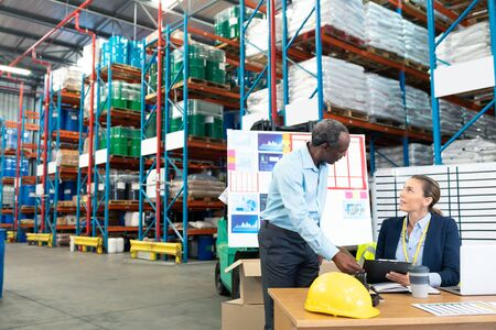 Front view of mature diverse male and female staffs discussing over clipboard at desk in warehouse. This is a freight transportation and distribution warehouse. Industrial and industrial workers concept