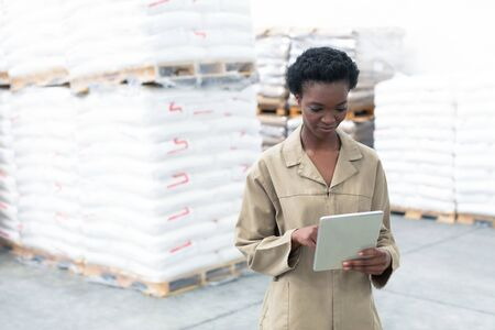 Front view of beautiful young African-american female worker working on digital tablet in warehouse. This is a freight transportation and distribution warehouse. Industrial and industrial workers concept