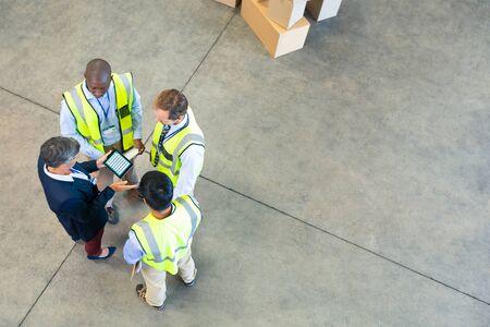 Hohe Betrachtungswinkel verschiedener Lagermitarbeiter, die über digitale Tablets im Lager diskutieren. Dies ist ein Gütertransport- und Distributionslager. Industrie- und Industriearbeiterkonzept