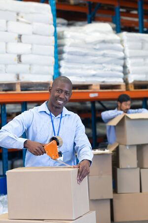 Portrait close-up of happy mature African-american male staff packing cardboard box with tape gun dispenser in warehouse. Asian male worker is unpacking cardboard box in the background. This is a freight transportation and distribution warehouse. Industrial and industrial workers concept