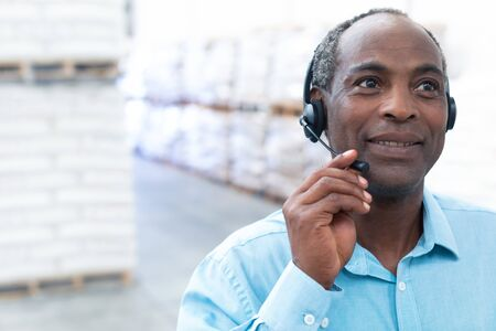 Portrait close-up of handsome mature African-american male supervisor talking on headset in warehouse. This is a freight transportation and distribution warehouse. Industrial and industrial workers concept Archivio Fotografico
