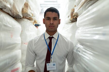 Portrait of handsome young Caucasian male supervisor looking at camera in warehouse. This is a freight transportation and distribution warehouse. Industrial and industrial workers concept
