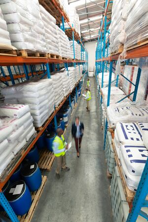 High angle view of diverse warehouse staff checking stocks in aisle in warehouse. They are holding clipboards and writing in it. This is a freight transportation and distribution warehouse. Industrial and industrial workers concept Standard-Bild