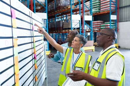 Side view of mature diverse warehouse staffs discussing over whiteboard in warehouse. This is a freight transportation and distribution warehouse. Industrial and industrial workers concept Banco de Imagens