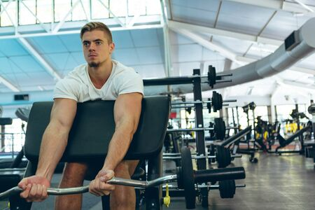Front view of concentrated fit young Caucasian male athletic exercising with barbell on preacher bench in fitness center. Bright modern gym with fit healthy people working out and training Stock Photo