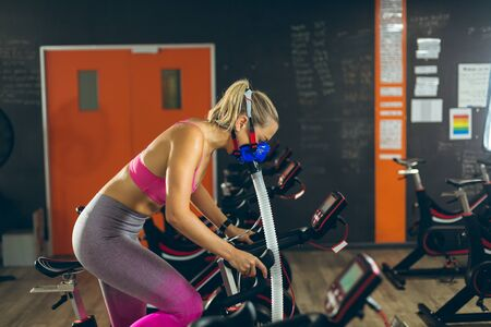 Side view of beautiful young Caucasian female athlete with oxygen mask exercising with exercise bike in fitness studio. Bright modern gym with fit healthy people working out and training