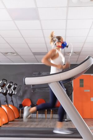 Side view of a Caucasian athletic woman doing a fitness test using a mask while using a treadmill inside a room at a sports center. Athlete testing themselves with cardiovascular fitness test on exercise bike