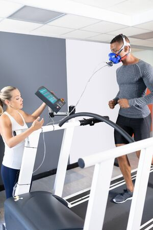 Side view of an African-American athletic man doing a fitness test using a mask connected to a monitor while riding a treadmill and a Caucasian woman assisting inside a room at a sports center. Athlete testing themselves with cardiovascular fitness test on exercise bike