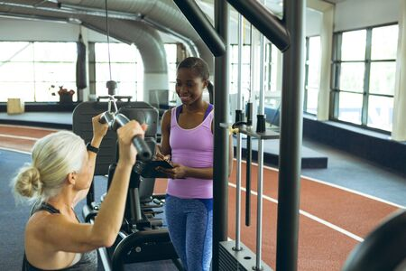 Side view of African-american female trainer assisting active senior Caucasian woman on lat pulldown machine in fitness studio. Bright modern gym with fit healthy people working out and training 写真素材