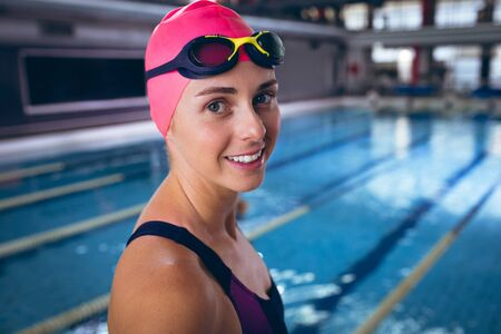 Side view of a Caucasian woman wearing a swimsuit and a pink swimming cap with goggles  smiling while standing by a pool inside a stadium