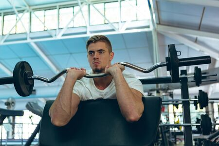 Front view of young Caucasian male athletic exercising with barbell on preacher curl in fitness center. Bright modern gym with fit healthy people working out and training
