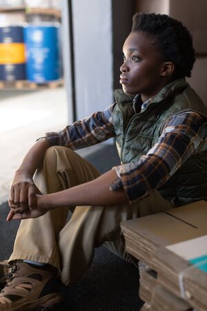 Close-up of thoughtful African-american female worker sitting in warehouse. This is a freight transportation and distribution warehouse. Industrial and industrial workers concept