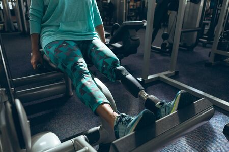 Low section of disabled active senior Caucasian woman with leg amputee exercising with leg press machine in fitness studio. Strong active senior female amputee training and working out Standard-Bild