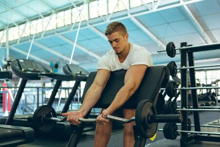 Front view of handsome fit young Caucasian male athletic exercising with barbell on preacher bench in fitness center. Bright modern gym with fit healthy people working out and training