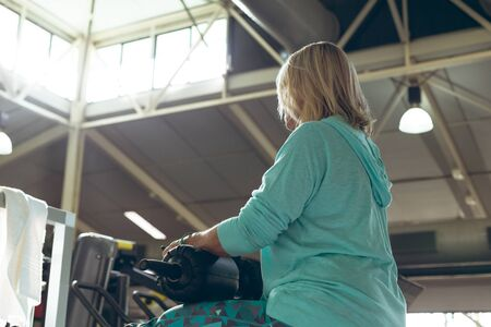 Low angle view of disabled active senior Caucasian woman exercising with leg curl machine in fitness studio. Strong active senior female amputee training and working out