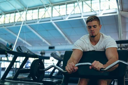 Front view of young concentrated Caucasian male athletic exercising with barbell on preacher bench in fitness center. Bright modern gym with fit healthy people working out and training Stock Photo