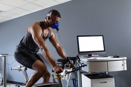 Side view of an African-American athletic man doing a fitness test using a mask connected to a monitor while riding an exercise bike inside a room at a sports center. Athlete testing themselves with cardiovascular fitness test on exercise bike