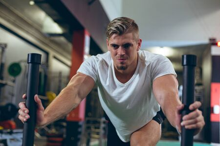 Front view of handsome young Caucasian  male athlete pushing prowler sled in fitness studio. Bright modern gym with fit healthy people working out and training
