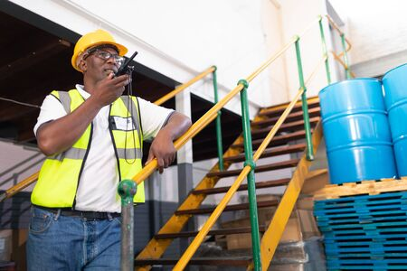 Low angle view of African-american male worker talking on talkie walkie in warehouse. This is a freight transportation and distribution warehouse. Industrial and industrial workers concept Banque d'images