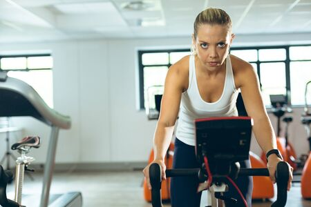 Front view of focused young Caucasian woman exercising with exercise bike in fitness studio. Bright modern gym with fit healthy people working out and training