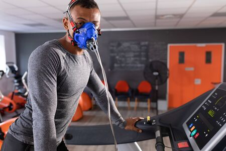 Side view of an African-American athletic man doing a fitness test using a mask while using a treadmill inside a room at a sports center. Athlete testing themselves with cardiovascular fitness test on exercise bike