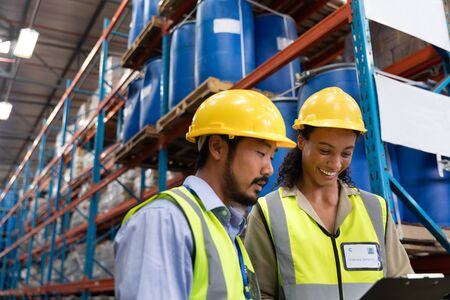 Low angle view of male and female worker discussing on clipboard in warehouse. This is a freight transportation and distribution warehouse. Industrial and industrial workers concept