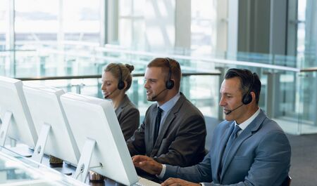 Business people with headset working on computer at desk in office. Modern corporate start up new business concept with entrepreneur working hard 免版税图像