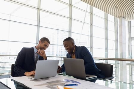 A young Caucasian businessman and an Afrcan American businessman sitting at a desk working together using laptops, smiling as they look at a smartphone. They are in front of the window in a modern office. Modern corporate start up new business concept with entrepreneur working hard Banco de Imagens