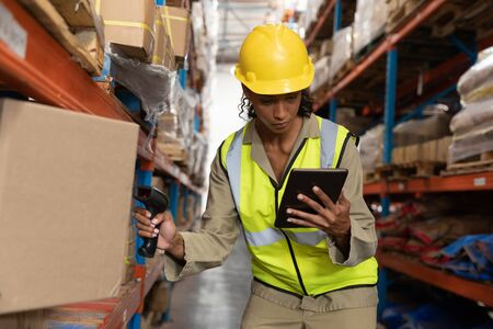 Front view of female worker scanning package with barcode scanner while using digital tablet in warehouse. This is a freight transportation and distribution warehouse. Industrial and industrial workers concept