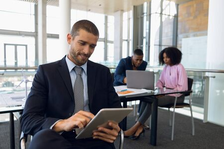 Close up front view of a smiling young Caucasian businessman sitting using tablet computer in an office. An African AMerican businessman and businesswoman work siting at desk in the background. Modern corporate start up new business concept with entrepreneur working hard Banco de Imagens