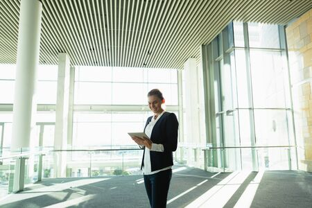 Happy businesswoman working on digital tablet in a modern office building. Modern corporate start up new business concept with entrepreneur working hard