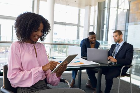 Close up side view of young African American businesswoman sitting using tablet computer in an office. A young African American and Caucasian businessman are sitting at a desk working with a laptop in the background. Modern corporate start up new business concept with entrepreneur working hard Banco de Imagens