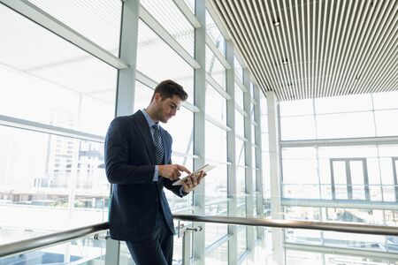 Side view of young Caucasian businessman standing using tablet computer leaning in the glass walled lobby of a modern business building. Modern corporate start up new business concept with entrepreneur working hard